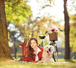Pretty female lying down with labrador retriever dog in a park