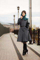 Sad young woman in grey classic coat with a handbag