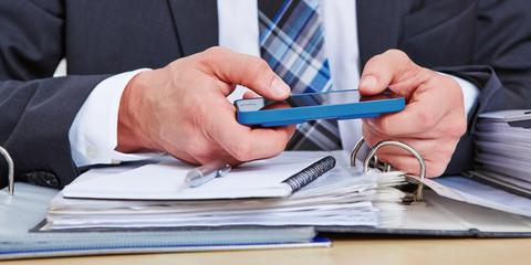 Manager mit Smartphone im Büro