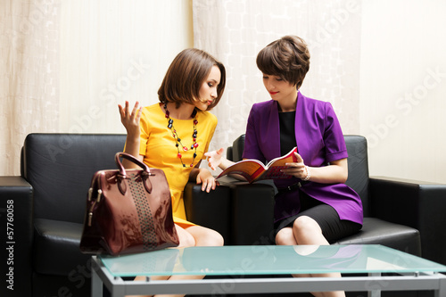 Two young women sitting on a couch in showroom