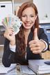 Frau im Büro mit Geld hält Daumen hoch