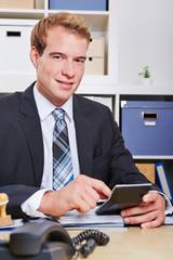 Mann mit Taschenrechner im Büro
