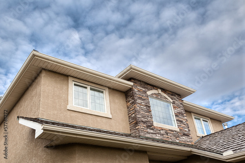 Roofline showing gutter, soffit, windows, roof and stones
