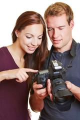 Model und Fotograf schauen Fotos auf Kamera an