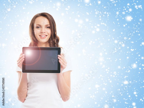 A young and happy girl in stylish jeans holding a tablet compute
