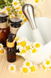 Essential oil and chamomile flowers in mortar on wooden table