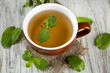 Cup of herbal tea with fresh mint flowers on wooden table