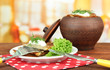 Potato pancakes in pot, on wooden table, on bright  background