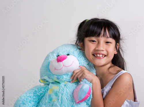 Cute, cheerful little girl holding blue bunny