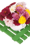 colorful flowers in a white vase, on a .wooden platform,