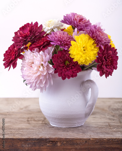 colorful flowers in a white vase on a wooden board