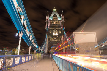 Detail of Tower Bridge in London at night with car light trail -