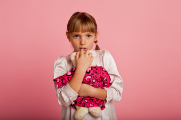 Little girl with a teddy bear looking freightened