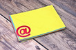 E-mail symbol and pile colorful envelopes on old wooden backgrou