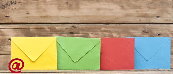 E-mail symbol and colorful envelopes on old wooden background