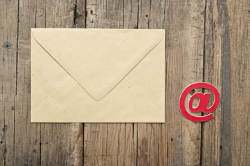 E-mail symbol and blank brown envelope on old wooden background