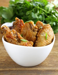 Fried chicken wings with hot  sauce in a white bowl