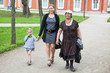 Grandmother, mother and young daughter walking in park at summer