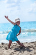 Posing on sand young girl in blue dress
