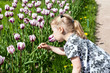 Small girl in summer dress smelling pink tulips