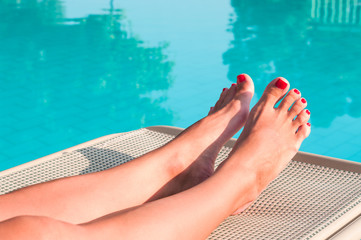 Female beauty feet with painted red nails laying on sunbed