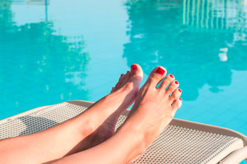 Female beauty feet with painted nails on a sunbed