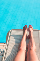 Beauty woman legs laying on beach bed near swimming pool