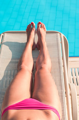 Female beautiful legs tanning near swimming pool