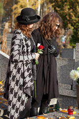 Women in mourning at cemetery in autumn