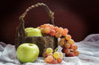 Apples and grapes with old basket