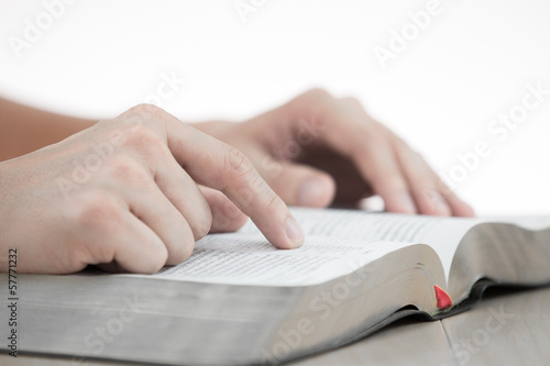 hands praying with bible