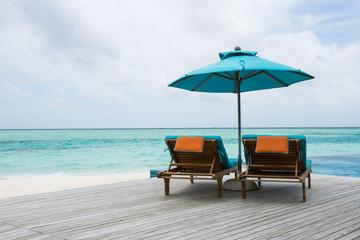 Sunbeds on wood deck by the beach