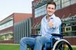 fröhlicher Rollstuhlfahrer zeigt Daumen