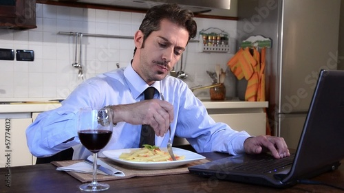 businessman eating pasta at home and working on computer