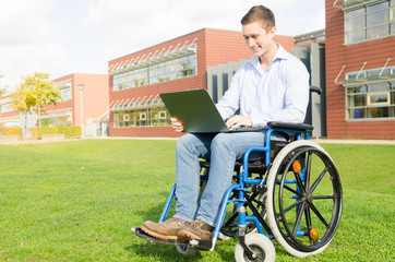 junger Rollstuhlfahrer mit Notebook