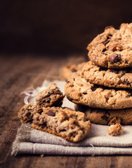 Chocolate chip cookies on natural linen napkin on wooden backgro