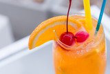 Orange juice in wine glass with cherry fruit