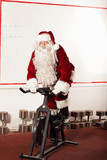 Santa Claus training on exercise bikes at the gym
