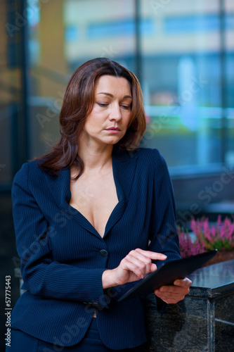 businesswoman with tablet outside
