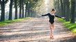 Young beautiful ballerina dancing outdoors in a parkway with tre