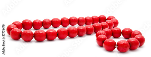 Red wooden beads and bracelet on a white background