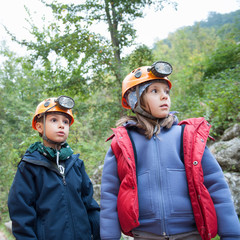 Young kids wearing helmet for cave exploration.