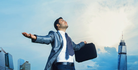 Successful businessman with arms outstretched celebrating succes