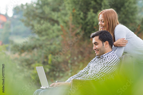 Couple or friends using laptop, outdoor - outside
