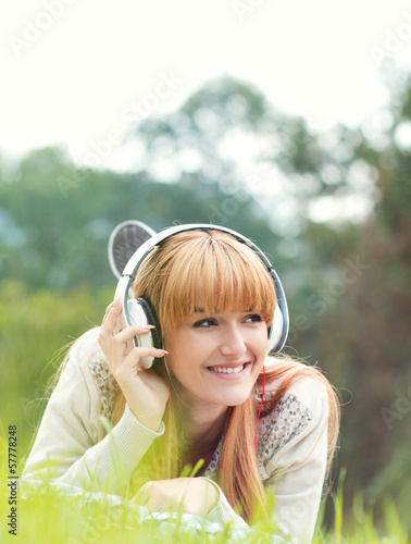Beautiful young woman with headphones. Enjoy music outdoors
