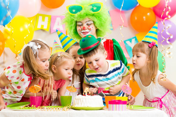 children with clown celebrating birthday party and blowing candl