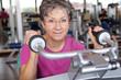 ältere Frau mit Brille trainiert im Fitnessclub