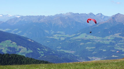 Colorful hang glider in sky over mountains, Kronplatz, Italy