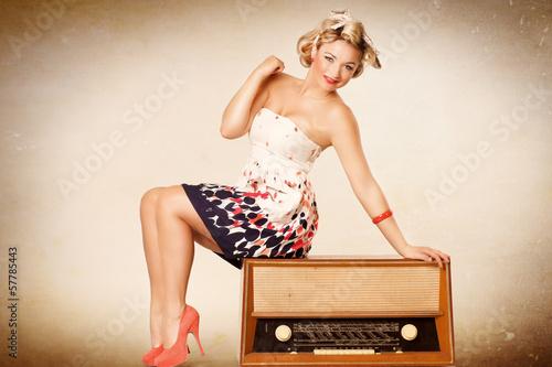 lachendes Pin up Girl sitzt auf Radio