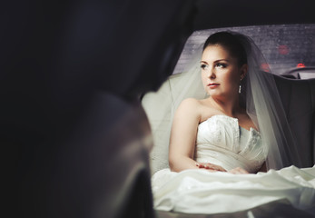 Caucasian young bride sitting in limo.
